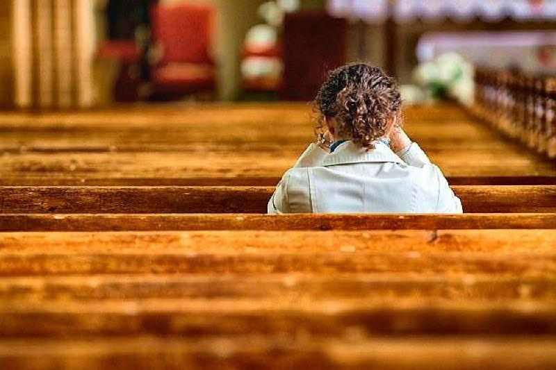 woman in church maybe crying and praying docu