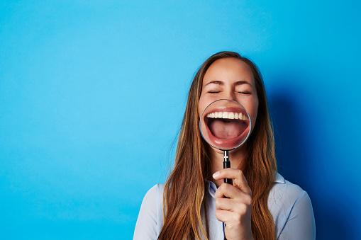 Beautiful woman laughing through magnifying glass